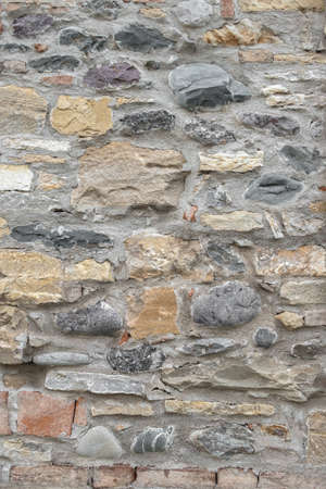Ancient wall made up of irregular stones with warm colors Stockfoto