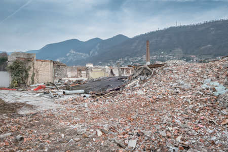 Demolition of buildings in urban environments. On background green mountains and a cloudy sky.