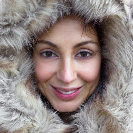 Closeup portrait of cute woman wearing warm coat with hood with fur, having fun in winter park, wintertime fashionable style, vacation concept.