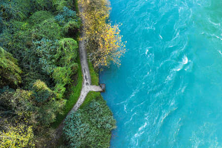 Top-down drone view of rapids of mountain river with small stone pier at the edge of the wood. Close up. Stock fotó