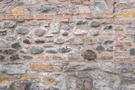 Ancient wall made up of irregular stones with warm colors Banco de Imagens