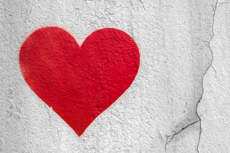Red love heart hand drawn on grungy wall. Textured background trendy street style.