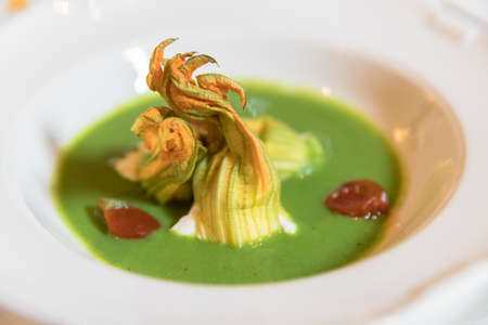 Plate of zucchini soup with pumpkin flowers and cherry tomatoes decoration. Served for wedding or event.