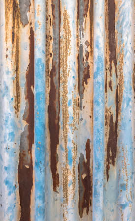 Old corrugated metal texture with rust spots on surface and peeled-off paint.