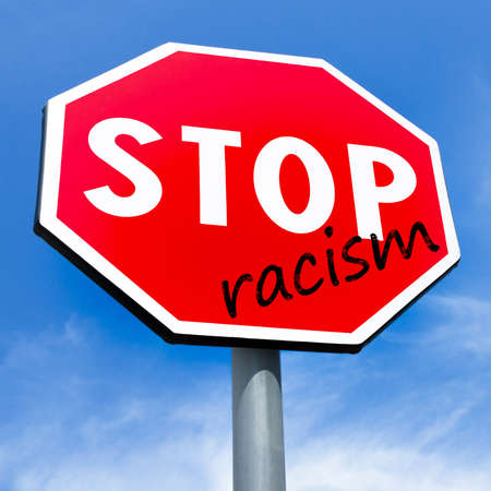 Red stop Racism sign on sky background. Design concept against racism, hating, discrimination.
