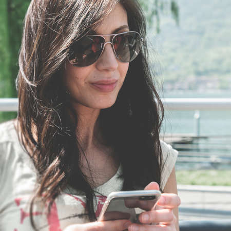 Young woman using smartphone. Urban women lifestyle technology. Vintage style. Soft focus.