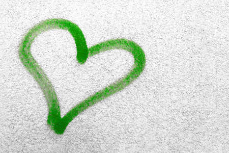 Concept or conceptual painted green abstract heart shape love symbol, dirty wall background, metaphor to urban and romantic valentine, grungy style. Banque d'images - 140989407