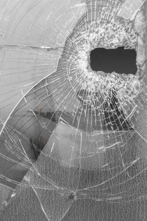 Broken glass with big hole. It can be used as backgrounds and concepts.