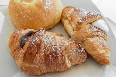 Two fresh italian croissants filled by vanilla and chocolate creams, accompanied by the round brioche with tuppo, on a white plate with napkins.