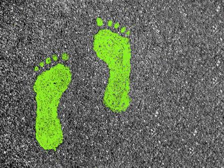 Green footprint signs on an asphalt road for pedestrian. Symbol of walkway.