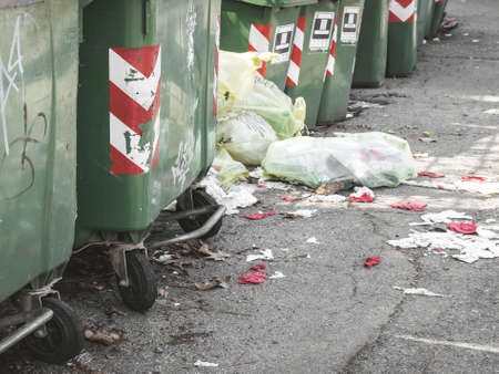 Abandoned garbage. Trash cans standing in a row ready to be collected on a residential street. On the ground, garbage bags that create pollution and dirt.