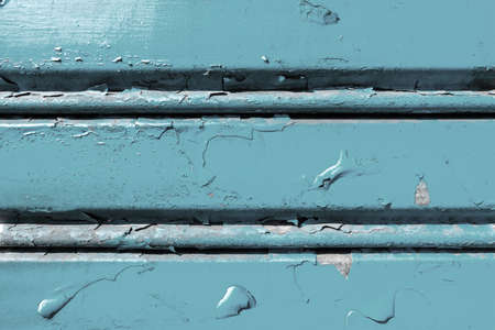 Background of old metal sheet with peel paint texture surface. Painted metal roller shutters door with peeling paint dirty light blue hue. Grungy background texture. Banque d'images - 140989525