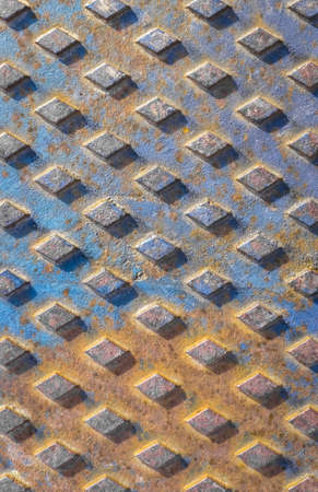 Old rusty drain cover background with diamond pattern. Orange and blue rusted manhole texture with square pattern, background macro.