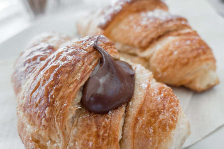 Two fresh italian croissants filled by  chocolate cream. Close-up.