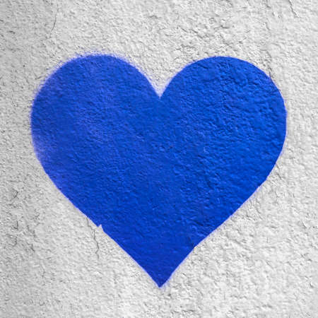 Blue love heart hand drawn on grungy wall. Textured background trendy street style. 版權商用圖片