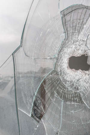 Glass broken with hole and splinters. Ideal for backgrounds and concepts.