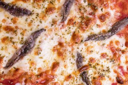 Pizza with tomato sauce, anchovies, mozzarella and oregano. Top view.