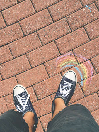 Sneakers on the road with a rainbow drawn. Spring and summer concept. Outdoor ideas and creativity.
