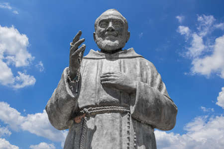 Statue of Saint Father Pio on sky background. Ideal for concepts or events.
