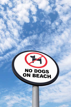 No dogs allowed sign on sky background. Dogs are not allowed on the beach at all times. Фото со стока
