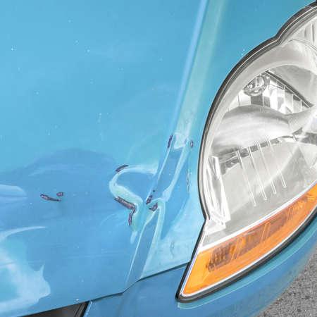 Damaged bodywork. Dents and scratch marks on a car's hood. Close-up.