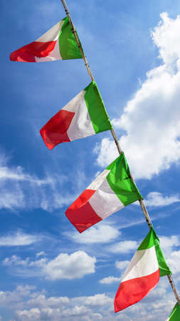 Small italian flags waving in the wind against blue sky