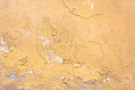 Grunge plaster wall with yellow scratched background. Old wall with peel swamp color stucco texture. Vintage wallpaper. Decay and cracks. Rough abstract surface.