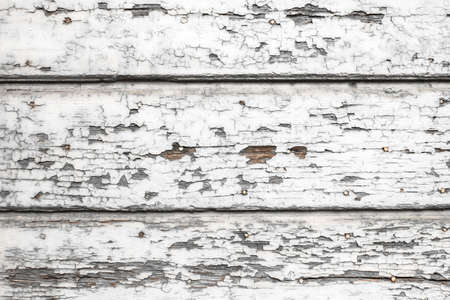 Old wooden painted white rustic fence, paint peeling background. Stock Photo