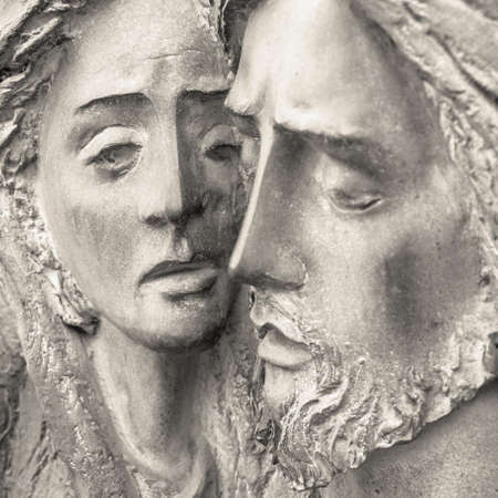 Faces of Holy Mary mother and Jesus Christ after the Crucifixion. Bas-relief in stone.