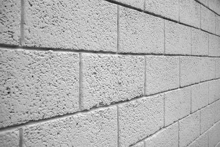 White brick block wall taken in an oblique corner. It can be used as background or texture.