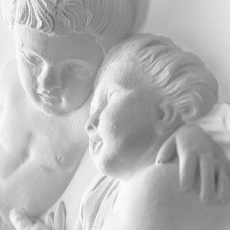 Statue of cherubs putti. Architecture detail of white plaster statue with cherubs (putti).