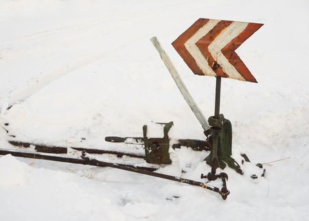 Railway switch path. Old vintage railway switching tracks under a thick layer of snow in the winter season at daytime. Stock Photo