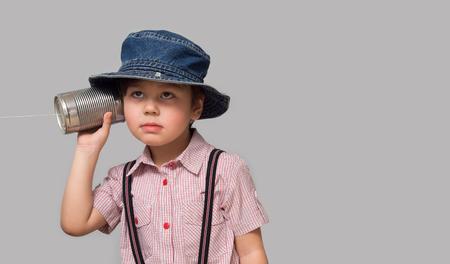Mały chłopiec przyczepił mu do ucha telefon z puszki Zdjęcie Seryjne