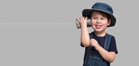 un petit garçon attaché un téléphone d & # 39 ; un anneau peut à son oreille Banque d'images