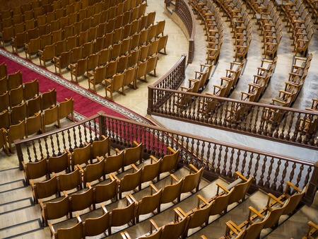 Rows of wooden chairs in a large auditorium