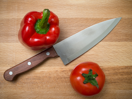 On a wooden board a bell pepper, a tomato and a knife