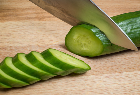 The knife cuts vegetables on a wooden cutting board. Foto de archivo