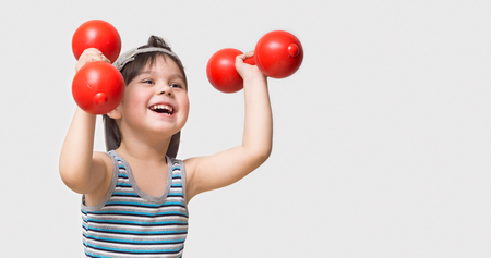 The child is engaged in physical training with red dumbbells