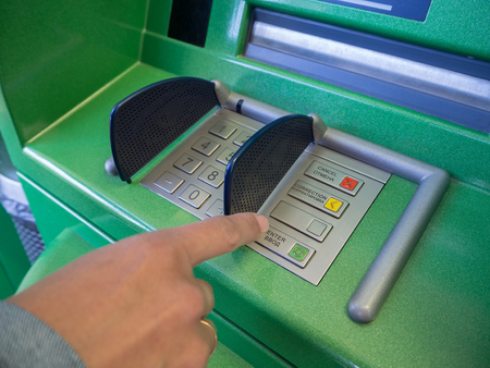Female hand presses ATM button. Cash machine green and female hand