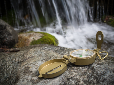 The compass lies on a stone against a waterfall background. Orientation in the forest 版權商用圖片