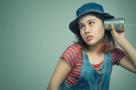 A girl attached a telephone from a tin can to his ear Reklamní fotografie