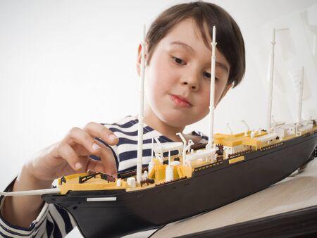 a little boy builds a model ship.