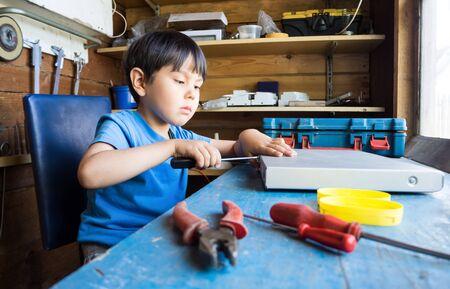 The boy makes in the workshop. Foto de archivo