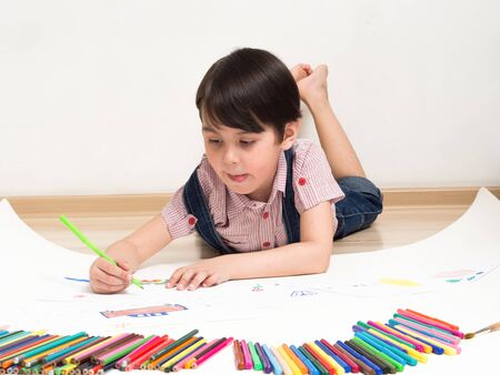 a small boy draws while lying on the floor.