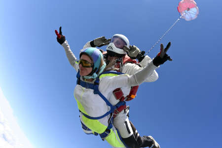 Tandem jump  The girl with the instructor in freefall  Standard-Bild