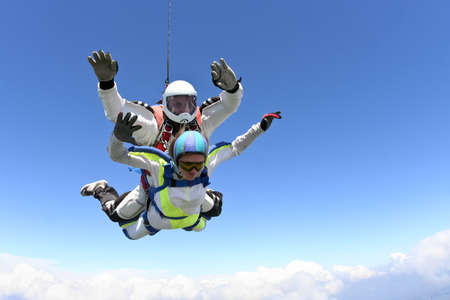 tandem: Tandem jump  The girl with the instructor in freefall  Stock Photo
