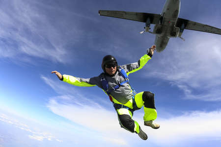The guy parachutist jumps out of an airplane