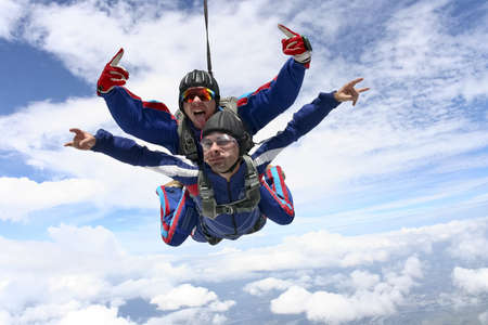 Tandem jump in the sky with clouds