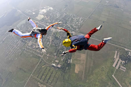 supervision: The student performs the task parachutist in free fall under the supervision of an instructor  Stock Photo