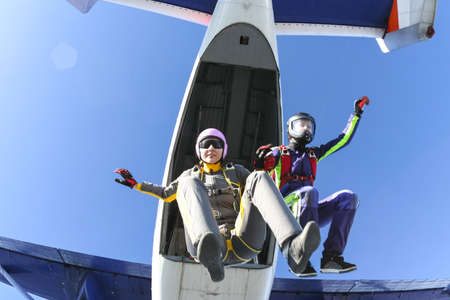 parachuting: Two girls parachutist jumping out of an airplane